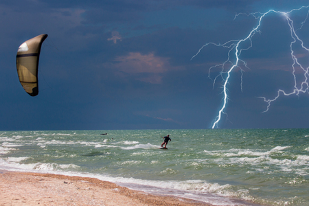 Thunderstorm in the stormy sky by the ocean. Kitesurfer Extreme rides a kite. Dangerous sport