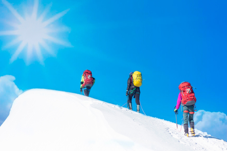 Professional hiking & climbing team. Sun day in snow mountains