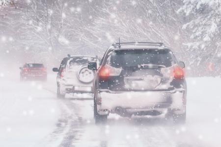 Winter, Schnee, Blizzard, schlechte Sicht auf der Straße. Auto während eines Blizzards auf der Straße mit den Scheinwerfern