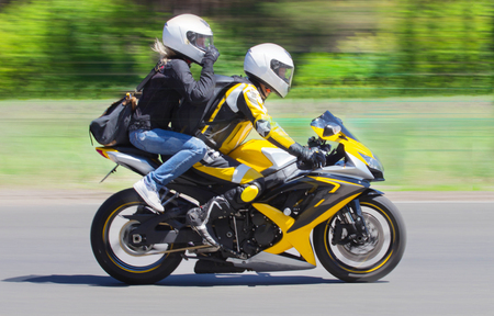 Active couple riding on the motorbike, slow motion, having fun in bikers tour, happy adventure concept on spring road. Banco de Imagens