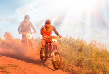 Unknown motorcycle racers overcomes motocross track in the fight for the championship at sunny day. Foto de archivo