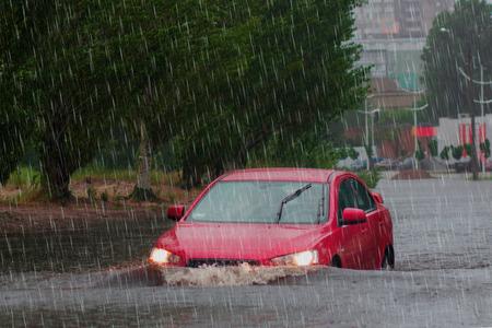 samochód jeździ w ulewnym deszczu na zalanej drodze.