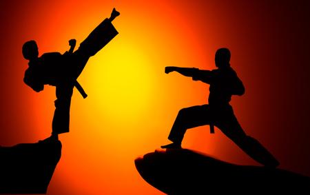 Mann, der nach Sonnenuntergang Karate am grasbewachsenen Horizont praktiziert. Kunst der Selbstverteidigung. Silhouette vor einem leuchtend orangefarbenen Himmel Standard-Bild