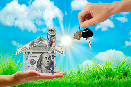 Money bags on hand and house key in hand and Sunlight represent Exchange or sell or contract for renting a house or real estate. Saving money or investing to buy a home or loan.