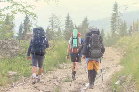 Group of hikers walking in mountains. Edges of the image are blurred,