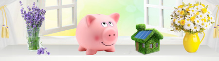 Real estate or home savings - red piggy bank, coins and a house Фото со стока