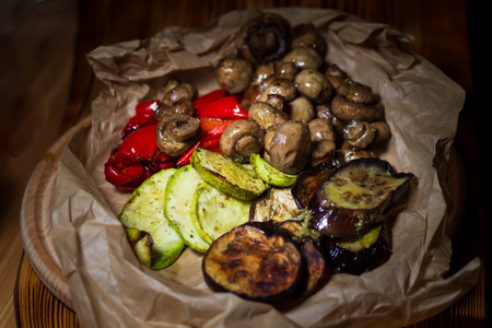 Mushrooms champignons and grilled vegetables: pepper, zucchini, tomatoes, cooked on a barbecue Фото со стока