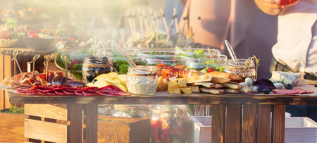 Beautifully decorated catering banquet table with different food snacks and appetizers with sandwich, on corporate christmas birthday kids party event or wedding celebration Stock Photo