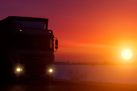 silhouette Truck with container on highway, cargo transportation concept. Sunset background Фото со стока