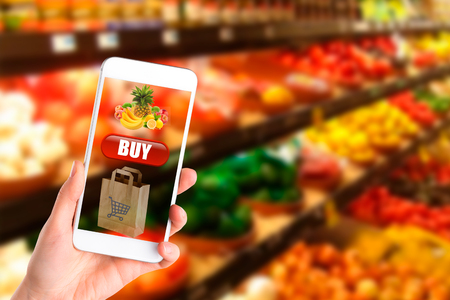 Woman shopping healthy food in supermarket background. Close up view girl buy products using digital gadget in store. Hipster at grocery using smartphone. Stock Photo