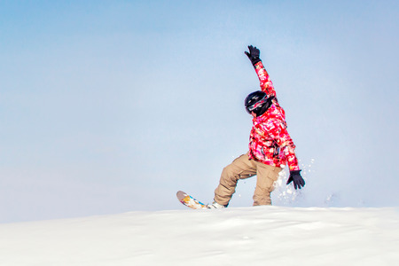 Snowboarder at jump inhigh mountains at sunny day.