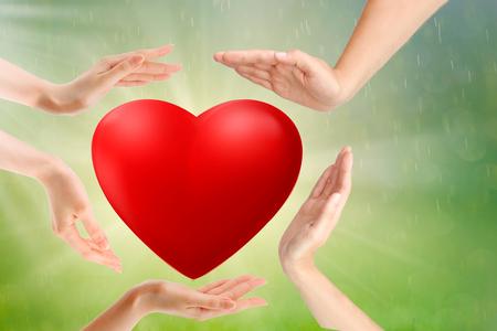 Manos de adultos y niños sosteniendo un corazón rojo, concepto de seguro de salud, amor y familia, día mundial del corazón,