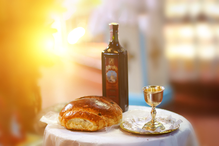 Holy communion on wooden table in church.Taking Communion.Cup of glass with red wine, bread on wooden table.The Feast of Corpus Christi Concept.Christians symbols concept.