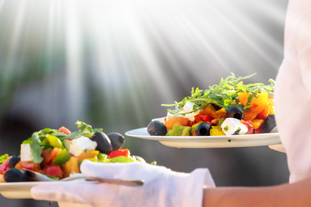 Waiter, carrying three plates with a rich salad Фото со стока