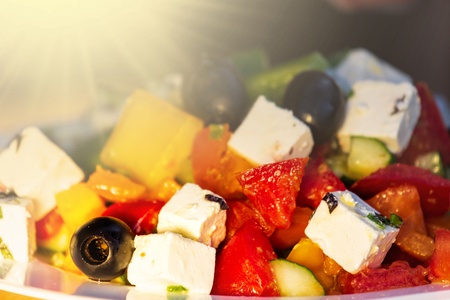 Greek salad of fresh cucumber, tomato, sweet pepper, lettuce, red onion, feta cheese and olives with olive oil. Healthy food, top view Фото со стока