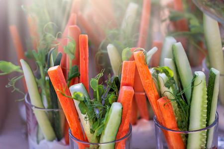 Colorful slices of raw vegetables in glasses (carrots, celery, cucumber, sweet pepper) and yogurt sauce. The concept of diet, healthy and vegetarian food. Selective focus