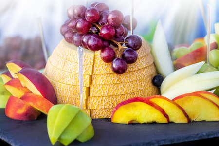 Assortment of exotic fruits on black table at sunny day.