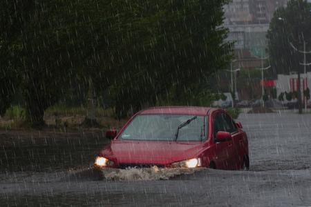 paseos en coche bajo una intensa lluvia en una carretera inundada Foto de archivo