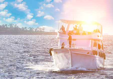 boat on on ocean water at sunrise with flare and outdoor lifestyle
