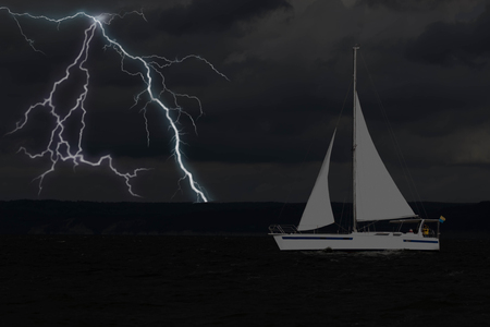 Sailing yacht in a stormy weather with lightning. Фото со стока