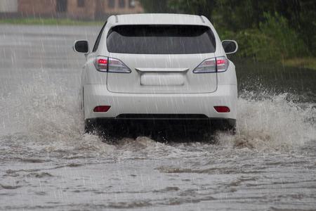 auto rijdt in zware regen op een ondergelopen weg