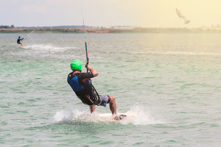 Kitesurfing. The young man is flying on the sea wave on the Board