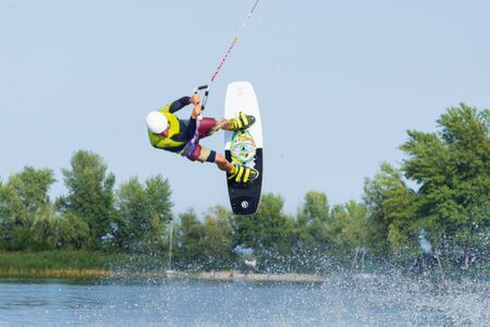 Cherkassy, Ukraine - July 19, 2019: Wakeboarder showing of tricks and skills at wakeboarding reverse event in Cherkassy Editorial