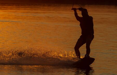 wakeboarder trains at sunset on the river