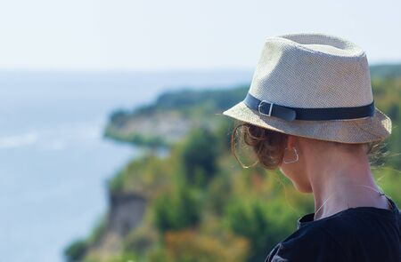 A woman looking to the sea in front of the beautiful sea sky and island view