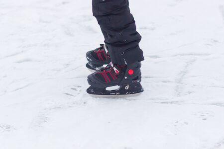 Red ice skates on frozen lake.