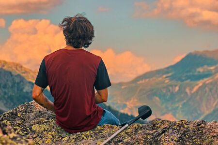 Young hiker in blue pants and shirt is sitting on cliffs edge, looking to misty hilly valley bellow.
