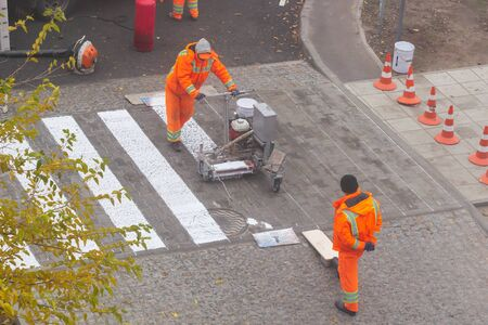 Traffic line painting. Workers are painting white street lines on pedestrian crossing. Road cones with orange and white stripes in background, standing on asphalt during road construction works Reklamní fotografie
