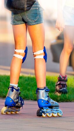 Beautiful long-legged girl posing on a vintage roller skates in denim shorts and white T-shirt in the skate park on a warm summer evening. Part of body. . 写真素材
