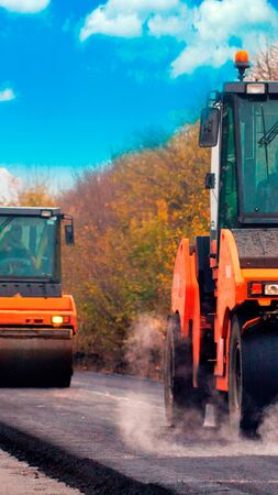 Road construction works with roller compactor machine and asphalt finisher. Vertical