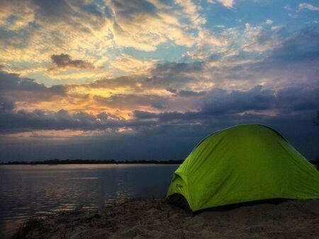 tourist tent and bikes near the blue lake, dramatic sky. Nature Stock Photo
