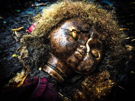 scary curly doll with a broken head Stock Photo