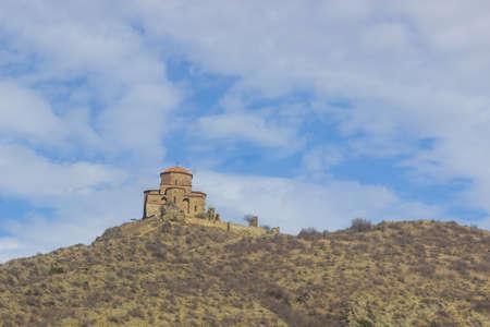 Mtskheta, Georgia. The Ancient Georgian Orthodox Church Of Holly Cross, Jvari Monastery With Remains Of Stone Wall, Heritage. Scenic Blue Cloudy Sky Background. Panorama