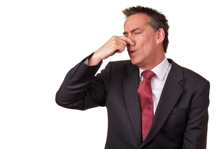 bad hair: Middle Age Businessman in Suit Smelling Something Bad Stock Photo
