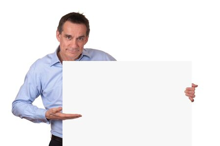 Attractive Middle Age Man in Blue Shirt Pointing to Blank White Sign on Right Stock Photo