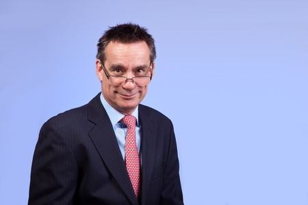 Smiling Business Man in Suit Looking Over Glasses on Blue Background photo