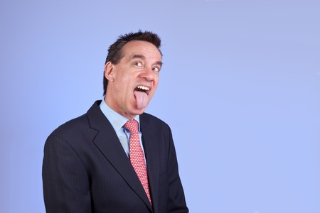 Attractive Business Man in Suit Sticking out Tongue on Blue Background photo