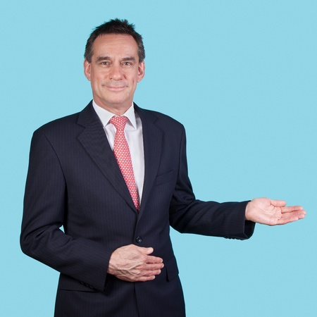 Handsome Smiling Business Man in Suit on Aqua Background Indicating Copy Space photo