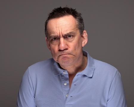 Handsome Middle Age Man Pulling Grimace Face and Glaring on Grey Background