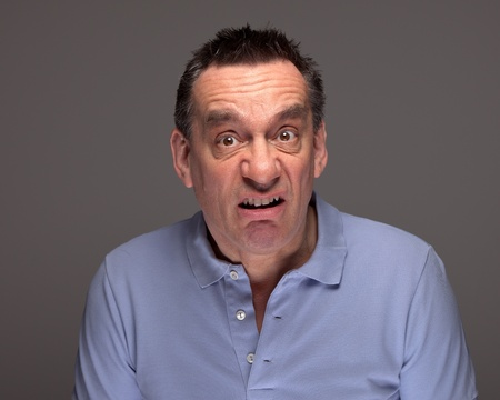 Middle Age Man Pulling Funny Grimace Face on Grey Background