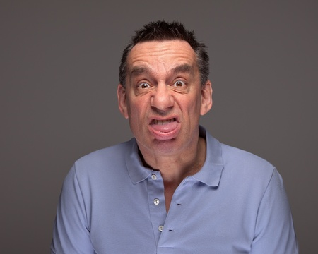 Handsome Middle Age Man Pulling Face Sticking Out Tongue on Grey Background