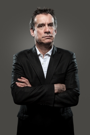 Grumpy Stern Middle Age Business Man in Suit Arms Folded Grey Background High Contrast Grunge Look Stock Photo