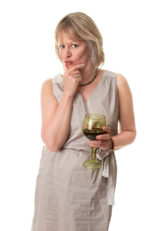 dismayed: Attractive Mature Woman Pursing Lips in Thought with Hand to Face Holding Wine Glass Isolated Stock Photo