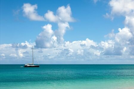 Beautiful Sunny Seascape with Anchored Yacht and Blue Sky with Fluffy Clouds photo