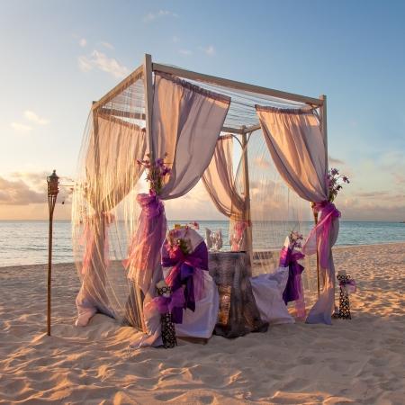 結婚式: 美しい日没時のサンディの熱帯のカリブ海のビーチでロマンチックな結婚式のテーブルの装飾