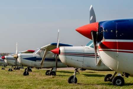 Cessna 152s Tied Down and Parked at Private Airfield against Blue Sky with Copy Space Stock Photo